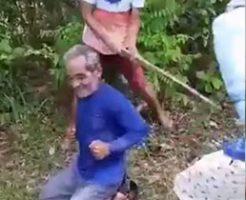ギャングに木材で拷問され高齢の男性や若者が苦しがっている姿