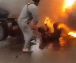 車の爆発事故で身体が真っ黒になっている男性を炎から引っ張る