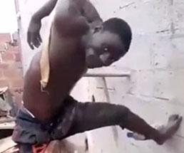 重りをつけられた状態で吊るされる男が必死に動き回る