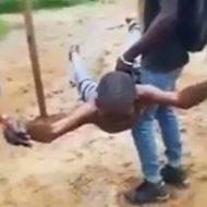 両手足を縛られ宙吊りにされる拷問を受けるおっさん
