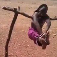 両手足を拘束され棒から吊るされる女性の苦しむ表情をご覧ください