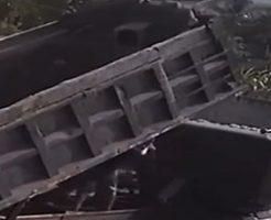 ダンプの開閉する荷台の下敷きになる作業員たち