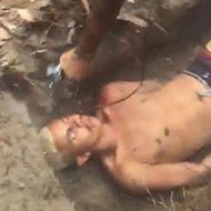 浅い墓穴の中で縛られた男が射殺され血まみれで息絶える